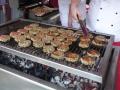 Frikadellen und Bratwürste bruzzeln auf dem Grill
