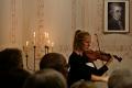 Oliwia Locher mit einem Bildnis von Wolfgang Amadeus Mozart im Hintergrund