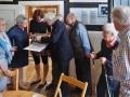 Job Schräder und Besucher schauen sich die Mappe mit Fotos zum Borgholzhausener Kartoffelmarkt an